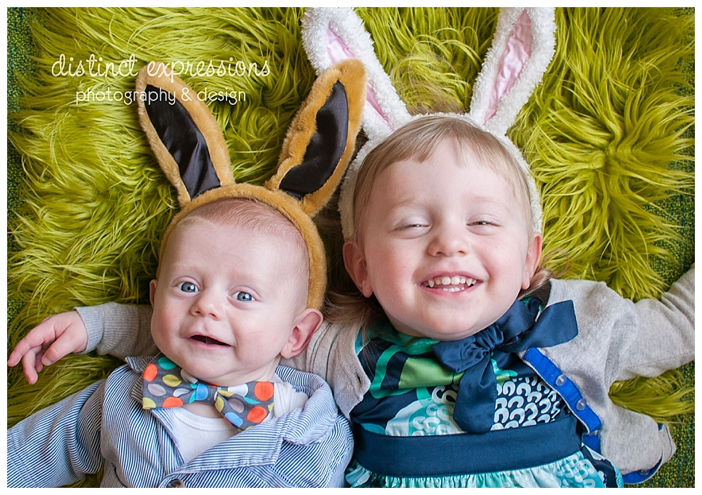 baby boy wearing pinstripe jacket bow tie bunny ears with big sister wearing Easter dress and rabbit ears