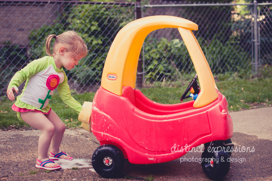 little girl wearing bathing suit washing toy push car in driveway in summer in grosse pointe, michigan